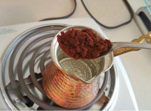 طرز تهیه قهوه ترک قهوه ترک چیست و چگونه تهیه میشود  ریختن پودر قهوه ارمنی در آب سرد